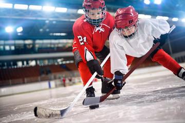 hokeista dzieci obsługi krążek na lodzie.