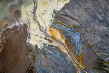 Top down view on abstract patterns and shapes of mineral waste rivers from power plant.