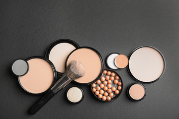 Flat lay composition with various makeup face powders on black background. Space for text