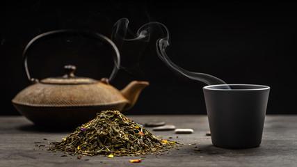 un tas de feuilles de thé avec une tasse et une théière en fond