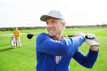 Mature grey-haired man with golf club behind back hit the ball during outdoor game