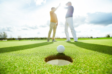 Golf ball lying on green play field close to hole with two successful players making high five on background