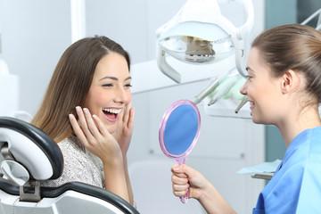 Szczęśliwy dentysty pacjent sprawdza wybielanie wynika