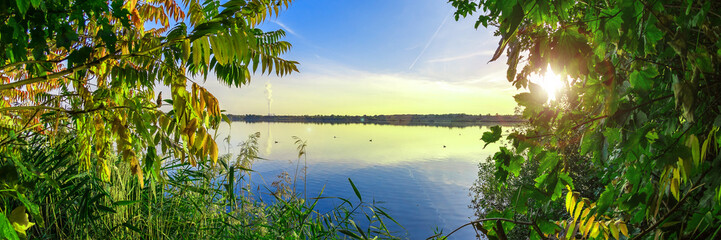 Zieleń liście przed błękitnym jeziorem, piękny natury tło