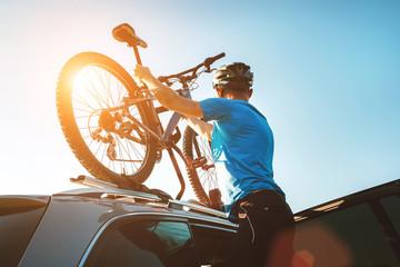 Mężczyzna rowerzysta górski zdjąć rower z dachu samochodu