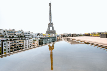 Beautiful cityscape view on Eiffel tower with reflection in the water during the daylight in Paris