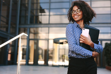 Happy business woman standing outside a office building