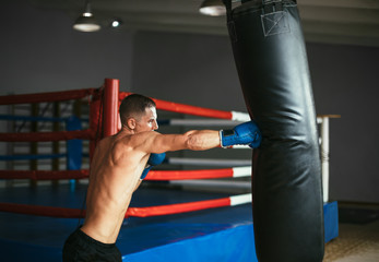 Male boxer hitting punching bag at a boxing studio