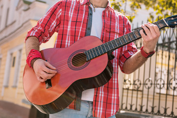 Another song. Close up of appealing male hands rising guitar and picking strings