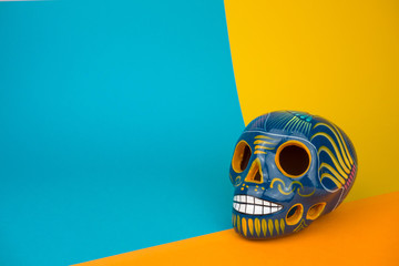 Creative and minimal Day of the Dead or Halloween layout. Skull on blue and orange paper background. Flat lay front view. Copy space..