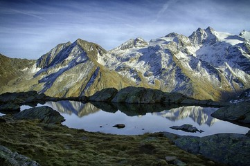 Great view of small lake in Gran Paradiso National Park,  Alps, Italy,  beautiful world. calm scenery with mountains covered by snow in background, majestic mountain landscape, wallpaper