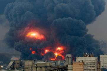Powerful explosion with bright flashes and black smoke in the city.