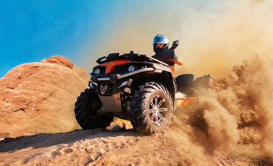 Quad bike in dust cloud, sand quarry on background
