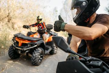 Jeździec ATV pokazuje kciuki do swojego partnera
