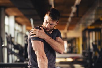 Przystojny młody człowiek czuje ból w ramieniu przy gym