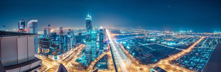 Spektakularna miejska panorama z kolorowymi iluminacjami miasta. Widok z lotu ptaka na autostradach i drapaczach chmur w Dubaju, Zjednoczone Emiraty Arabskie.