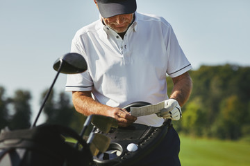 Senior man reading his scorecard while out playing golf