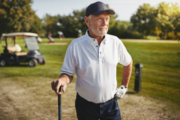 Senior man looking down the fairway of a golf course
