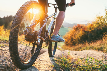 Mountain biker ride down from hill. Close up wheel image. Active and sport leisure concept