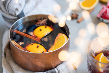 Mulled wine hot drink with oranges and spices in copper pot