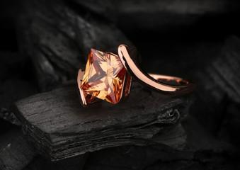 pierścionek z biżuterią z dużym klejnotem topazowym na tle czarnego węgla
