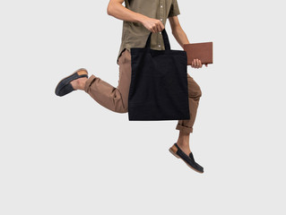 Man jump is holding bag canvas fabric for mockup blank template isolated on gray background.