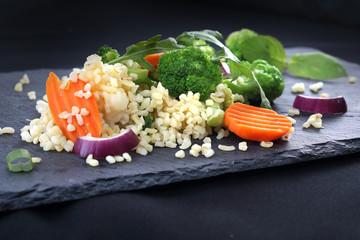 Lekka dieta, ryż z brokułami i marchewką. Ryż brązowy z warzywami podana czarnym talerzu.