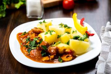 gulasz wieprzowy podawany z gotowanymi ziemniakami