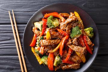Na stole smażona wołowina teriyaki z czerwoną i żółtą papryką, brokułami i sezamem. poziomy widok z góry