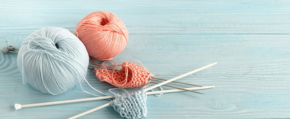 Knitting wool and knitting needles in pastel blue and pink colors on blue  wooden background. top view.copy space.banner