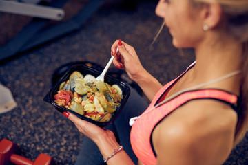 Odgórny widok je zdrowego jedzenie kobieta podczas gdy siedzący w gym. Pojęcie zdrowego stylu życia.