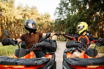 Dwóch jeźdźców ATV uderza pięściami na szczęście, widok z tyłu