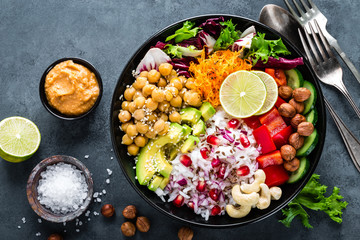 Healthy vegetarian Buddha bowl with fresh vegetable salad, rice, chickpea, avocado, sweet pepper, cucumber, carrot, pomegranate and nuts closeup