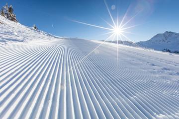 Fresh snow on ski slope during sunny day.