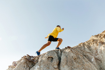 concept to overcome difficulties. man in sports clothes climbing steep mountain