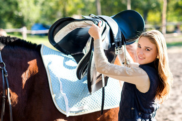Girl equestrian rider equips horse