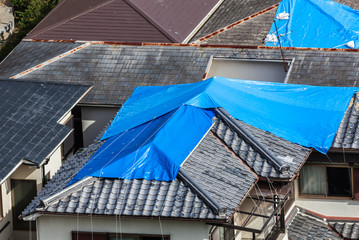 High angle view of houses hit by natural disaster, with damaged tiled roof covered with blue tarp