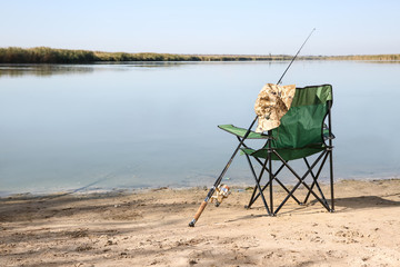 Camping chair and fishing rod at riverside on sunny day. Space for text