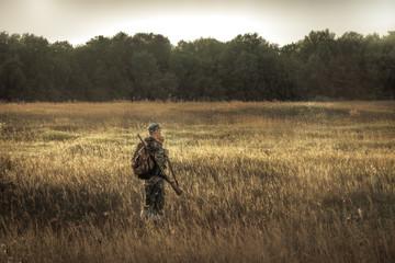 myśliwy polowanie na wiejskim polu w pobliżu lasu o zachodzie słońca w sezonie polowań