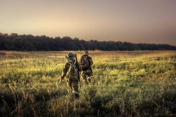 Myśliwi z wyposażeniem łowieckim odchodzącym przez wiejskie pole w kierunku lasu o zachodzie słońca podczas sezonu łowieckiego na wsi