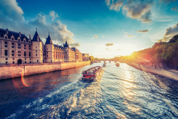 Dramatic sunset over river Seine in Paris, France, with Conciergerie and Pont Neuf. Colourful travel background. Romantic cityscape.