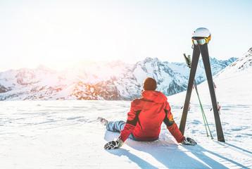 Narciarz sportowiec siedzi w górach Alpy w słoneczny dzień - dorosły mężczyzna, ciesząc się zachodem słońca z biegami nieba obok niego - koncepcja sportów zimowych i wakacji