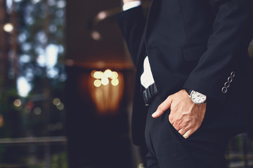 Atrakcyjny młody człowiek w ciemnym garniturze i zegarku na nadgarstku, który wkłada rękę do kieszeni spodni