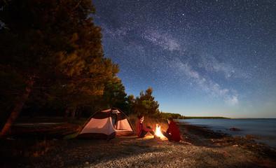 Nocne biwakowanie na brzegu. Mężczyzna i kobieta wycieczkowiczom odpoczywa przed namiotem przy ogniskiem pod wieczór niebem pełnym gwiazd i Mlecznym sposobem na błękitne wody i lasu tle. Koncepcja życia na świeżym powietrzu