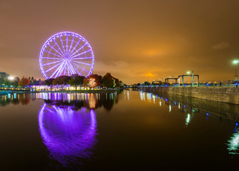 A brightly lit ferris wheel in the old port area of Montreal, Canada. Beautifully reflected in the water
