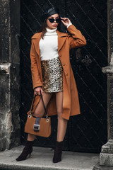 Outdoor full body fashion portrait of  elegant woman wearing glasses, beret, turtleneck, leopard printed skirt, camel color coat, ankle boots, holding suede handbag, posing in street of european city