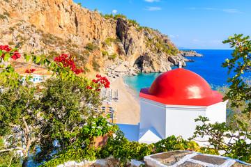 Typical Greek chapel overlooking Kyra Pynagia bay with beautiful beach on Karpathos island, Greece