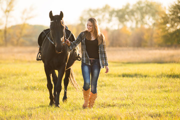 Dziewczyna jeździec stoi w pobliżu konia i przytula konia. Motyw konia