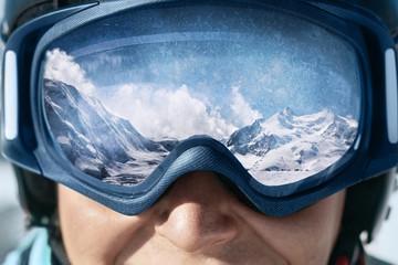 Zamyka up narciarskie gogle mężczyzna z odbiciem zaśnieżone góry. Pasmo górskie odbite w masce narciarskiej. Mężczyzna na tła niebieskim niebie. Noszenie okularów narciarskich. Sporty zimowe.