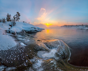 Winter rocky bay to the lake. Dawn, dawn in the winter in the gulf of the lake. Lake in the winter in the ice, snow.